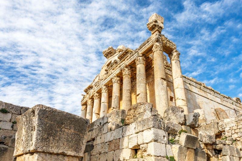 Kolommen van oude Roman tempel van Bacchus met het omringen van ruïnes en blauwe hemel op de achtergrond, Beqaa-Vallei, Baalbeck, royalty-vrije stock foto's