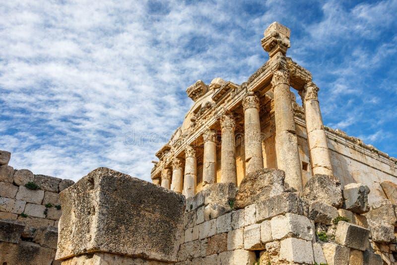 Kolommen van oude Roman tempel van Bacchus met het omringen van ruïnes en blauwe hemel op de achtergrond, Beqaa-Vallei, Baalbeck, royalty-vrije stock afbeelding