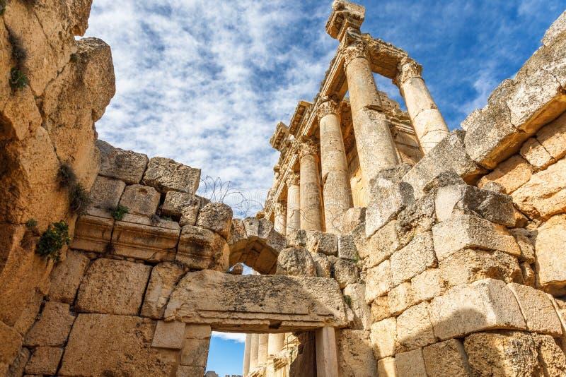 Kolommen van oude Roman tempel van Bacchus met het omringen van ruïnes en blauwe hemel op de achtergrond, Beqaa-Vallei, Baalbeck, stock foto