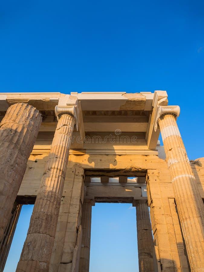 Kolommen van Propylaea-ingangsgateway van Akropolis, Athene, Griekenland de zonsondergang overzien en de stad die stock foto