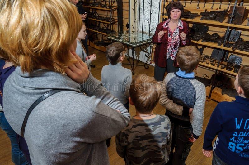 Kolomna, Russie - 3 janvier 2017 : visiteurs de musée de Settlement de forgeron de Femelle-guide parmi photos stock