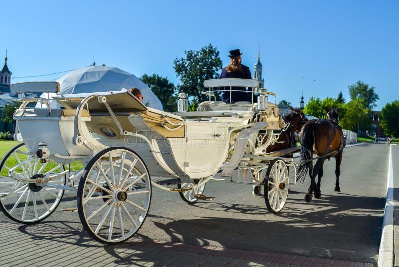 Kolomna Ryssland - Augusti 11, 2018 Elegant vit vagn med kuskar i svart hatt och bruna hästar som bär turister arkivbilder