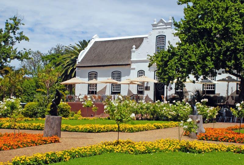 Koloniale landbouwbedrijfhuis en bloemen (Zuid-Afrika) stock fotografie