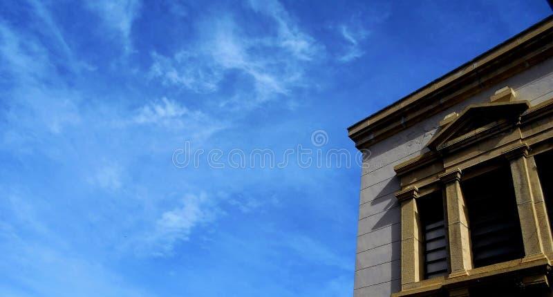 Kolonialny okno z niebieskiego nieba tłem zdjęcia royalty free