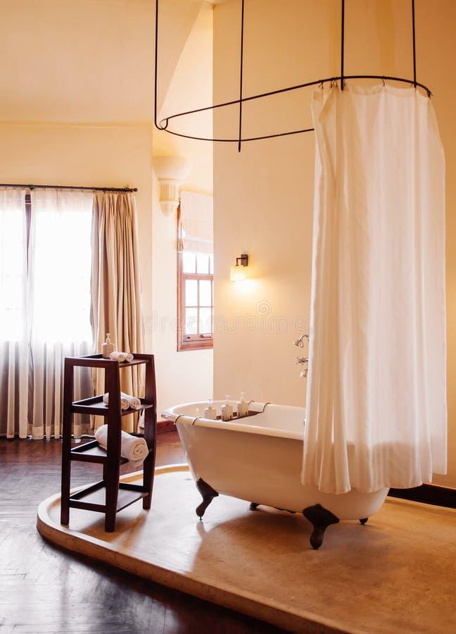 Kolonialt badrum för tappning med det vita retro clawfootbadkaret royaltyfri foto