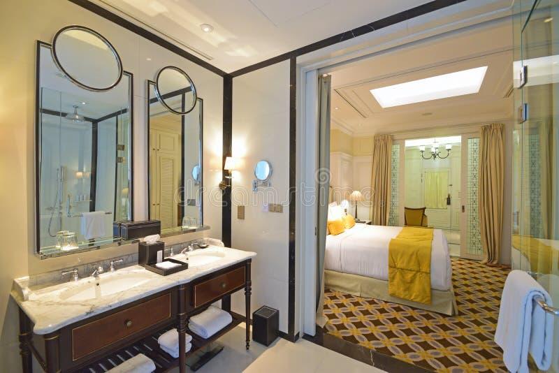 Kolonialt vagelhotellrum med klassisk badrumdesign och det eleganta sovrummet royaltyfri bild
