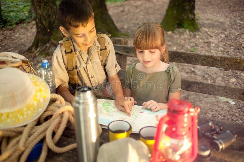Kolonier spanar barn som campar och, läser översikten arkivbild