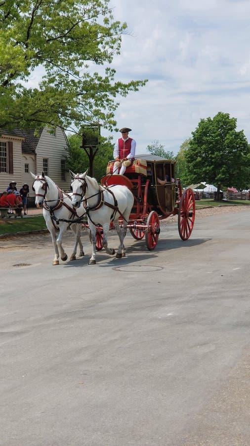 KoloniinvånareWilliamsburg arkitektur och lopp Utdragna vagnsritter för häst med turister arkivbilder