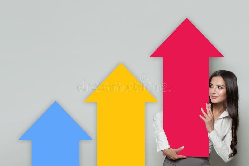 Kolonner för pil för resning för visning för affärskvinna som föreställer affärstillväxt Affärsframgång och aktier Up begrepp arkivfoton