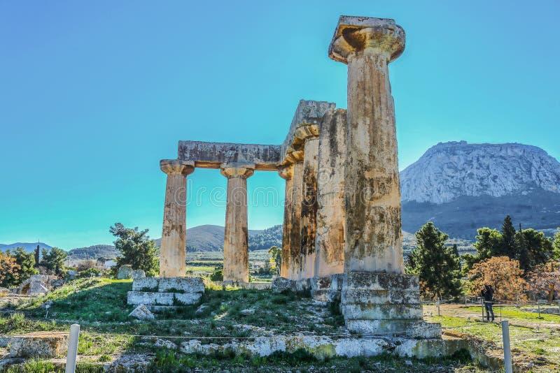 Kolonner fördärvar in av templet av Apollo med Acrocorinth akropolen av forntida Corinth - ett monolitiskt vaggar kontroll det fo royaltyfria bilder