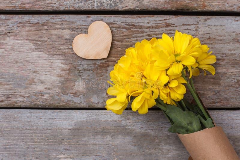 Kolorów żółtych kwiaty i woodedn serce fotografia stock