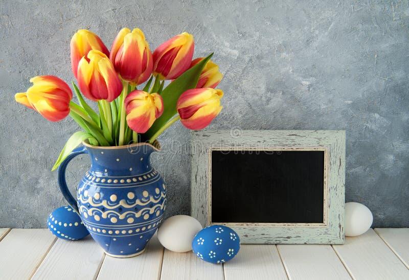 Kolorów żółtych tulipany w błękitnym ceramicznym miotaczu z Wielkanocnymi jajkami i a fotografia royalty free