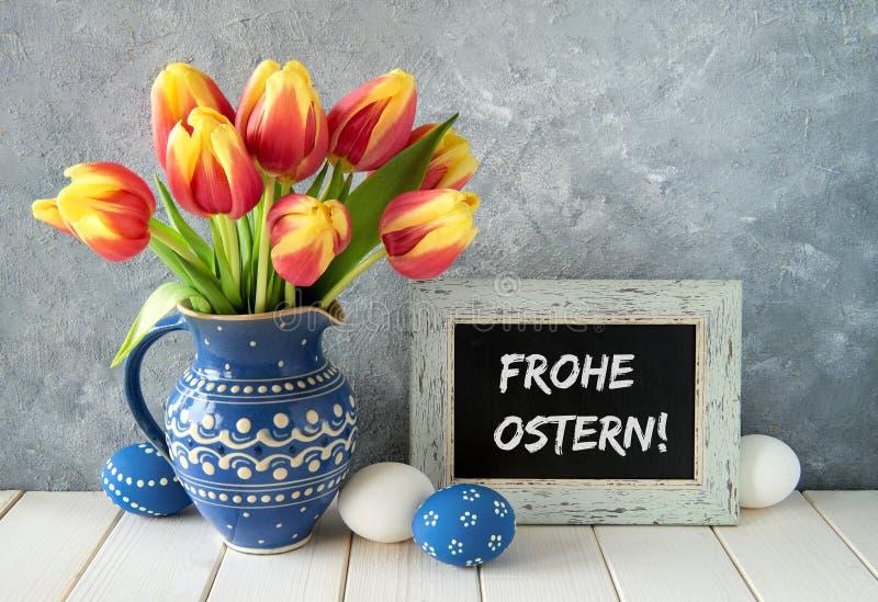 Kolorów żółtych tulipany w błękitnym ceramicznym miotaczu z Wielkanocnymi jajkami i a zdjęcia royalty free