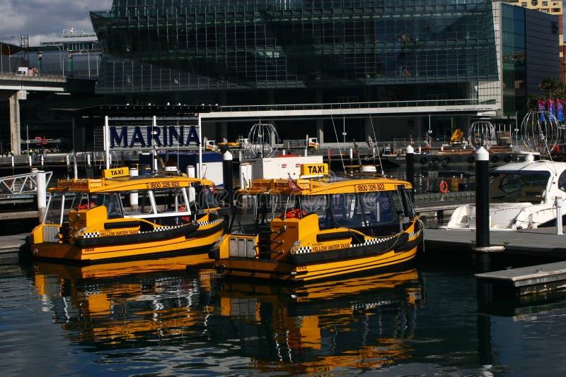 Kolorów żółtych wodni taxi zakotwiczający przy molem w marina z nowożytnym szklanym budynkiem w Cockle zatoce, Kochany schronieni obraz stock