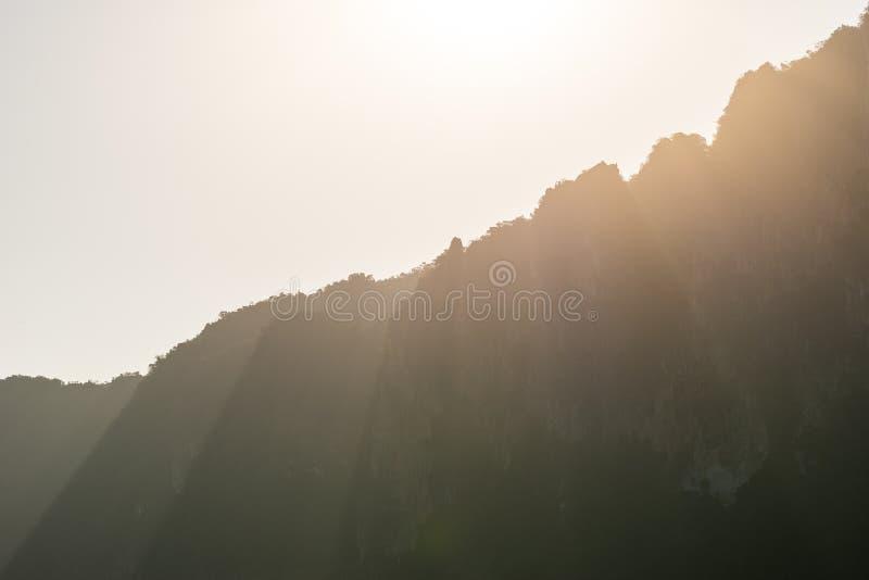 Kolorów ciepli promienie światło słoneczne spadają przez szczytów góry w mgiełce obrazy stock