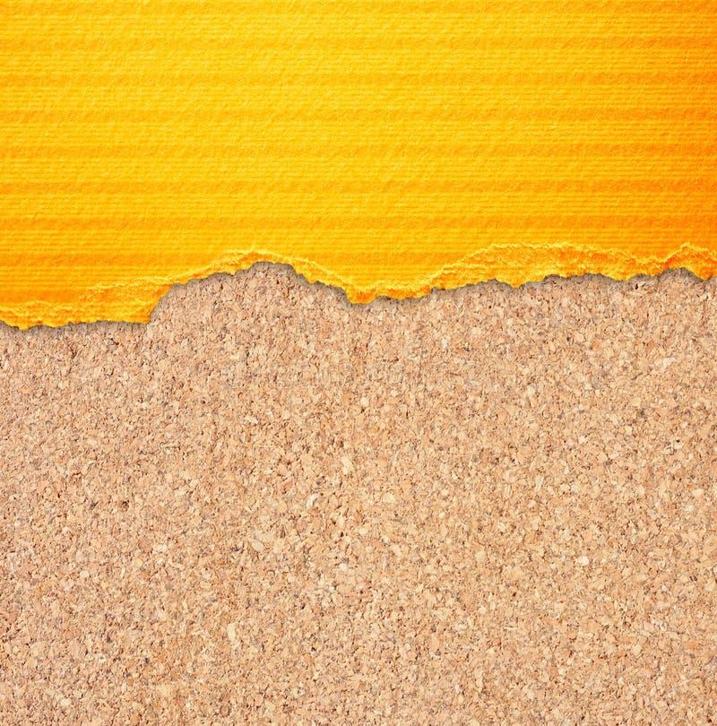 Kolor żółty drzejący papier z lampasami nad korek deski tłem. fotografia royalty free