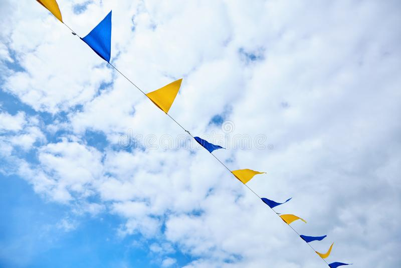 Kolor żółty i błękitny trójgraniasty festiwal zaznaczamy na nieba tle z białymi chmurami Plenerowy świętowania przyjęcie świątecz obrazy royalty free