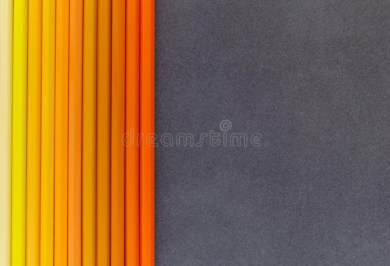 Kolor żółty i pomarańcze barwiliśmy ołówki na ciemnego tła odgórnym widoku obrazy royalty free