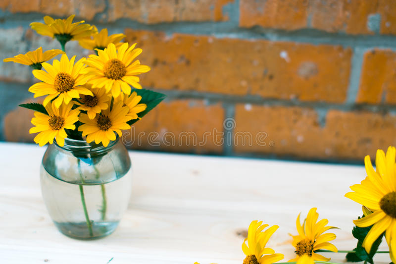 Kolor żółty kwitnie na drewnianym stole z zamazanym tłem zdjęcie stock
