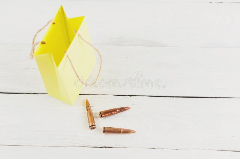 Kolor żółty papierowa paczka i trzy pociska na starych białych drewnianych deskach zdjęcia royalty free
