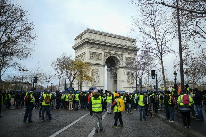 Kolor żółty przekazuje protestującego przed Arc De Triomphe na czempionach Elysees - Gilets jaunes protesty - obraz royalty free