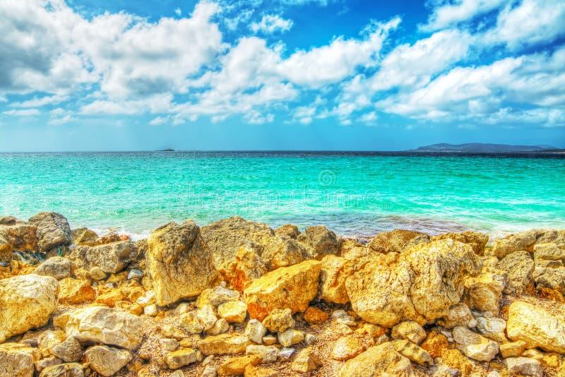 Kolor żółty skały i błękitny morze w Alghero obraz stock