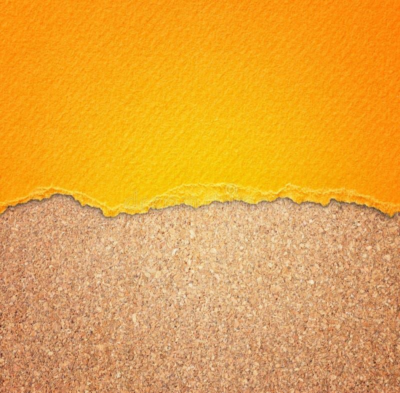 Kolor żółty textured poszarpanego papier nad korek deski tłem. zdjęcia royalty free