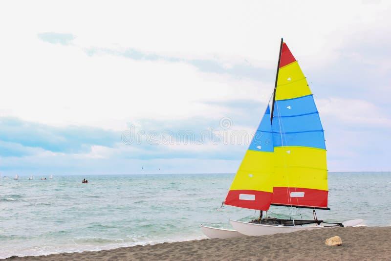 Kolorowa żeglowanie łódź na plaży na chmurnym dniu zdjęcie royalty free