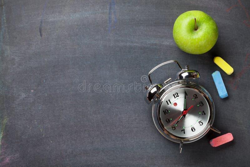 Kolorowa kreda, budzik i jabłko na blackboard tle, obrazy royalty free