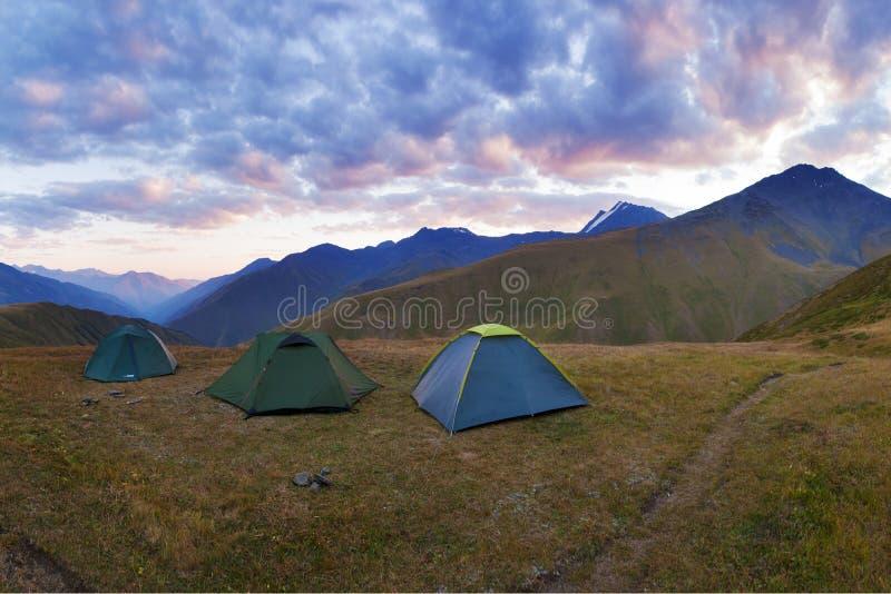 Kolorowa lato panorama z zielonymi turystycznymi namiotami na dolinie pod górami pod niebieskim niebem Piękny halny dziki zdjęcia royalty free