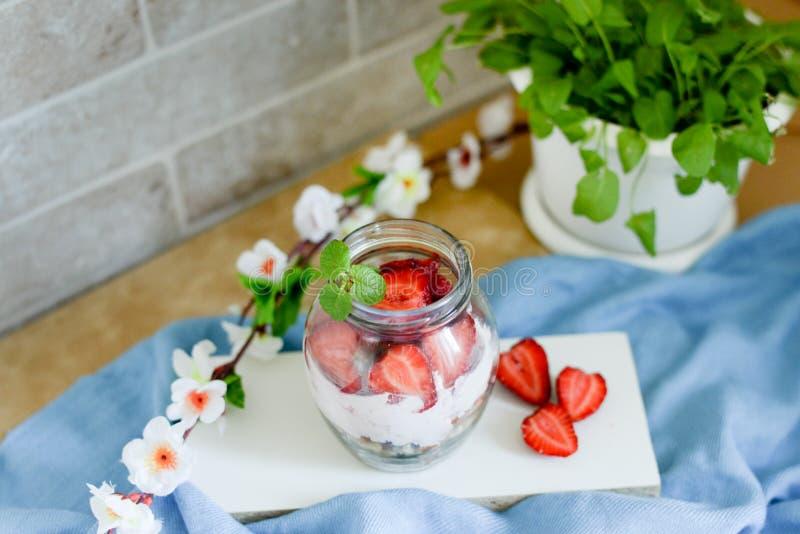 Kolorowa owocowa sałatka w słoju na białym i błękitnym nieociosanym drewnianym tle Odgórny widok Truskawkowy milkshake w słoju zdjęcie royalty free