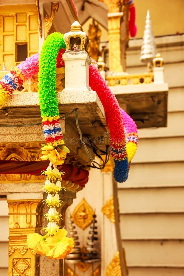 Kolorowa plastikowa kwiat girlanda na Tradycyjnej Tajlandzkiej plenerowej ducha domu świątyni zdjęcia royalty free