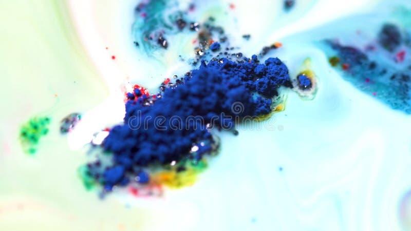 Kolorowa prochowa farba na mleku W górę prochowej farby unosi się ruchy na powierzchni biały ciecz Zdruzgotany kolorowy obraz stock