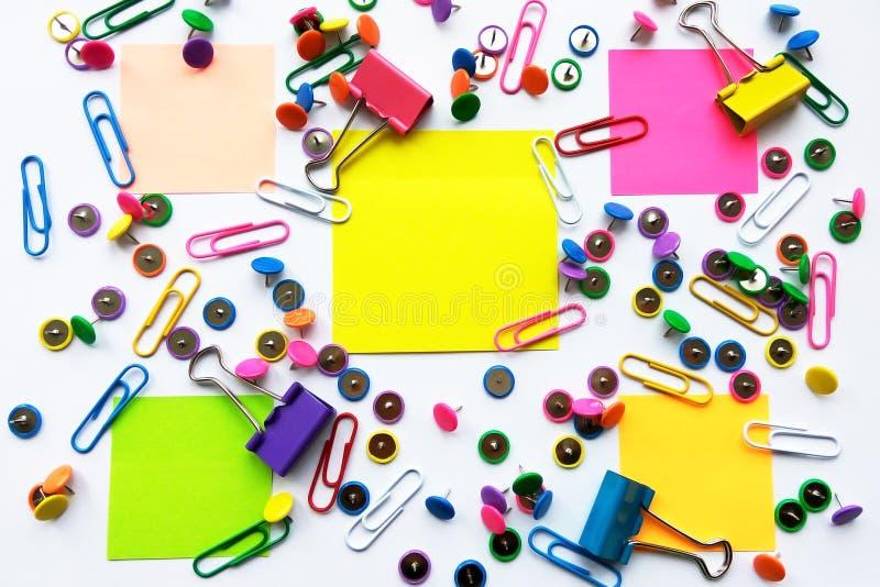 Kolorowa szkoła i biurowych dostaw papierowe klamerki, szpilki, żółte notatki, majchery na białym tle zdjęcie stock