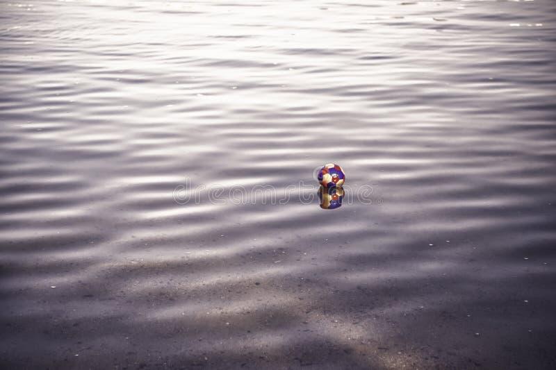 Kolorowa zabawkarska piłka, meczu futbolowego atrybut odbija w falistej wodzie fotografia stock