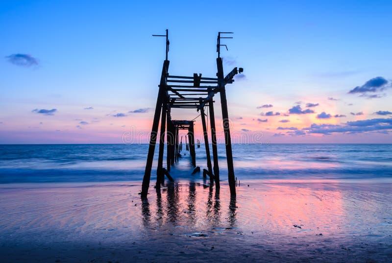 Kolorowa zmierzch plaża z zaniechanym drewnianym molem fotografia royalty free