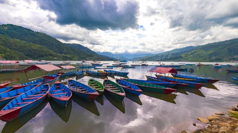 Kolorowe łodzie w Phewa jeziorze coludy dAay Nepal zdjęcia stock