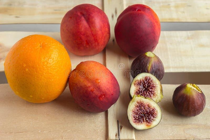 Kolorowe świeże owoc - pomarańcze, figi i brzoskwinie, kłamają na woode obrazy stock