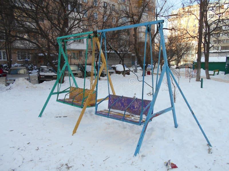 Kolorowe children huśtawki w śniegu parkują teren †‹â€ ‹miasto fotografia royalty free