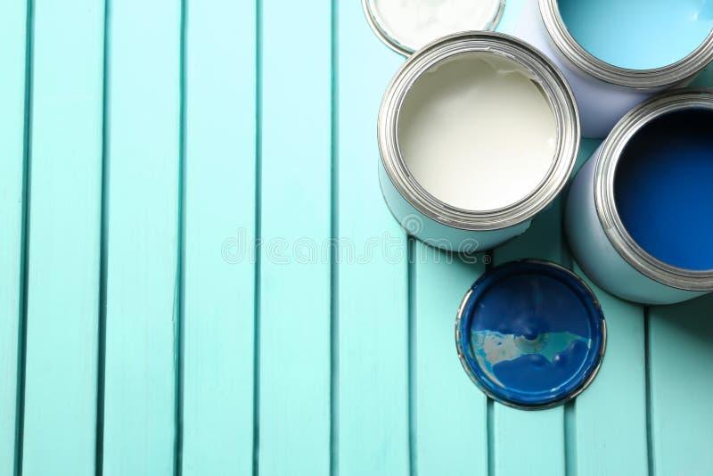 Kolorowe farb puszki na błękitnym drewnianym tle, odgórny widok obrazy stock