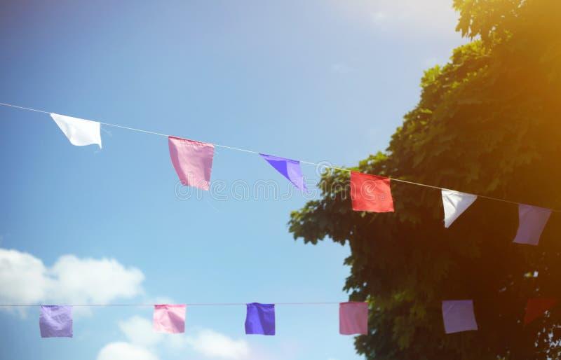 Kolorowe flagi przeciw niebieskiemu niebu z bia?ymi chmurami Lata przyj?cia lub festiwalu uliczny poj?cie fotografia stock