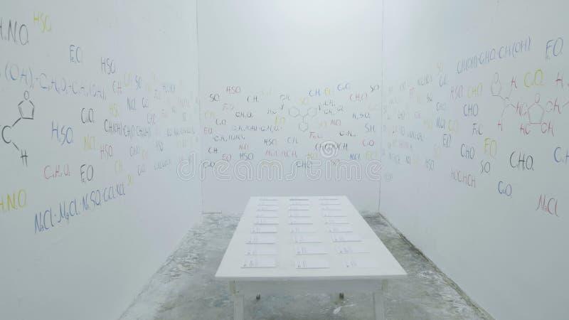Kolorowe formuły chemiczni elementy na ścianach przy białym biura i bielu stołem Chemiczne formuły pisać na bielu fotografia royalty free