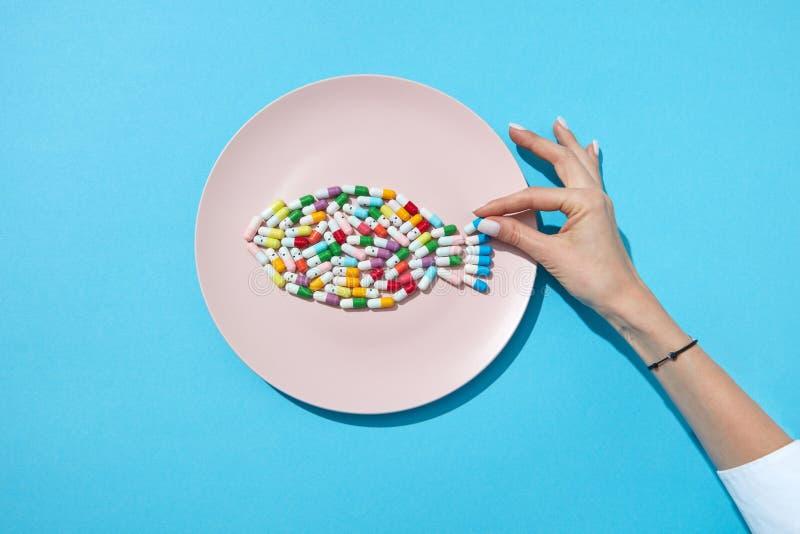 Kolorowe kapsuły i pigułki na talerzu w kształcie ryba z kobiety ręką na błękitnym tle i cieniach, kopia zdjęcia royalty free