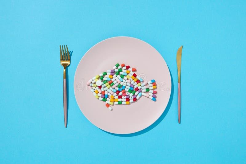 Kolorowe kapsuły i pigułki w postaci ryby na talerzu z rozwidleniem i nożem na błękitnym tle, kopii przestrzeń wierzchołek fotografia royalty free