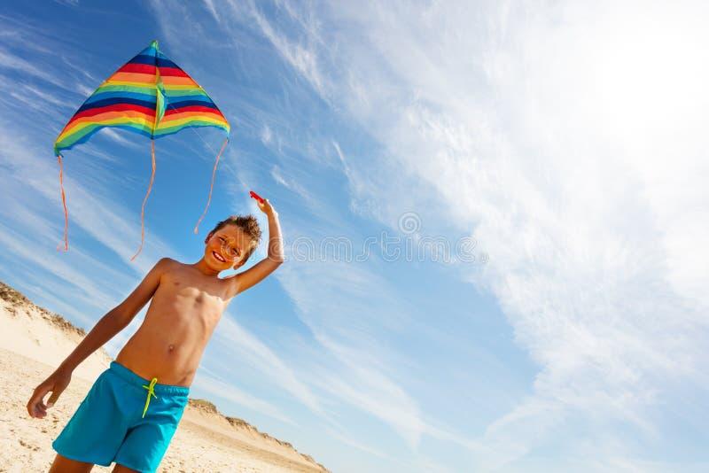 Kolorowe latawce trzymane przez chłopca na plaży nad niebieskim niebem obraz royalty free