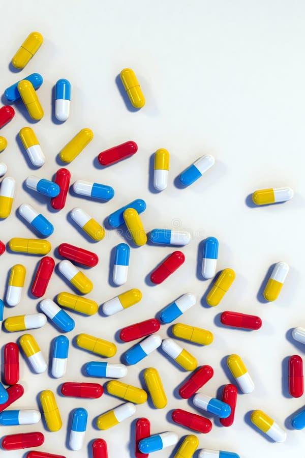 Kolorowe medycyn kapsuły na bielu stole, pionowo royalty ilustracja