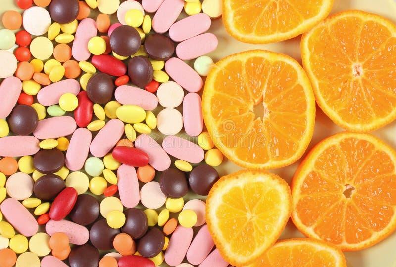 Kolorowe medyczne pigułki i świeża pomarańcze jako tło, opieka zdrowotna i zdrowy stylu życia pojęcie, zdjęcia stock