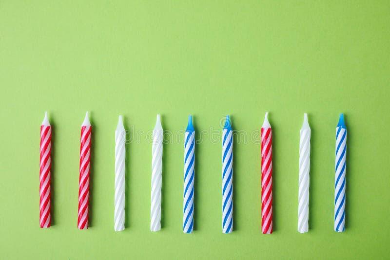 Kolorowe pasiaste urodzinowe świeczki na zielonym tle obraz stock