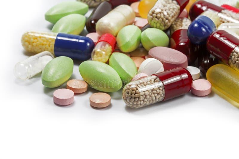 Kolorowe pigułki i medyczne kapsuły jako narożnikowy tła isola zdjęcie stock