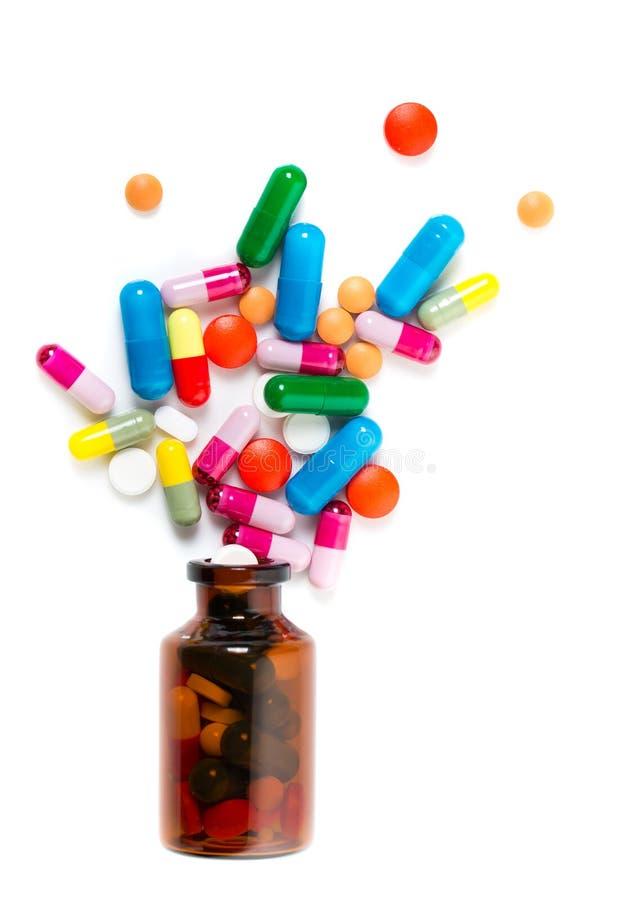 Kolorowe pigułki rozlewa z przewracającej się jaskrawej czerwonej pomarańczowej pigułki butelki zdjęcie royalty free